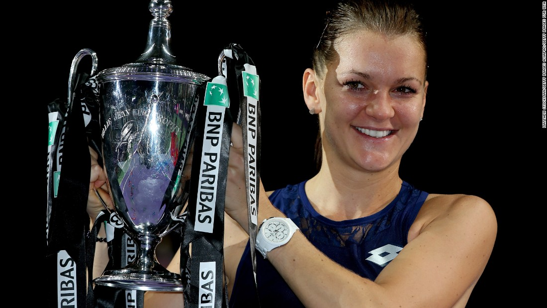 Agnieszka Radwanska of Poland holds aloft the Billie Jean King Trophy after defeating Petra Kvitova of Czech Republic in the title match of the WTA Finals.