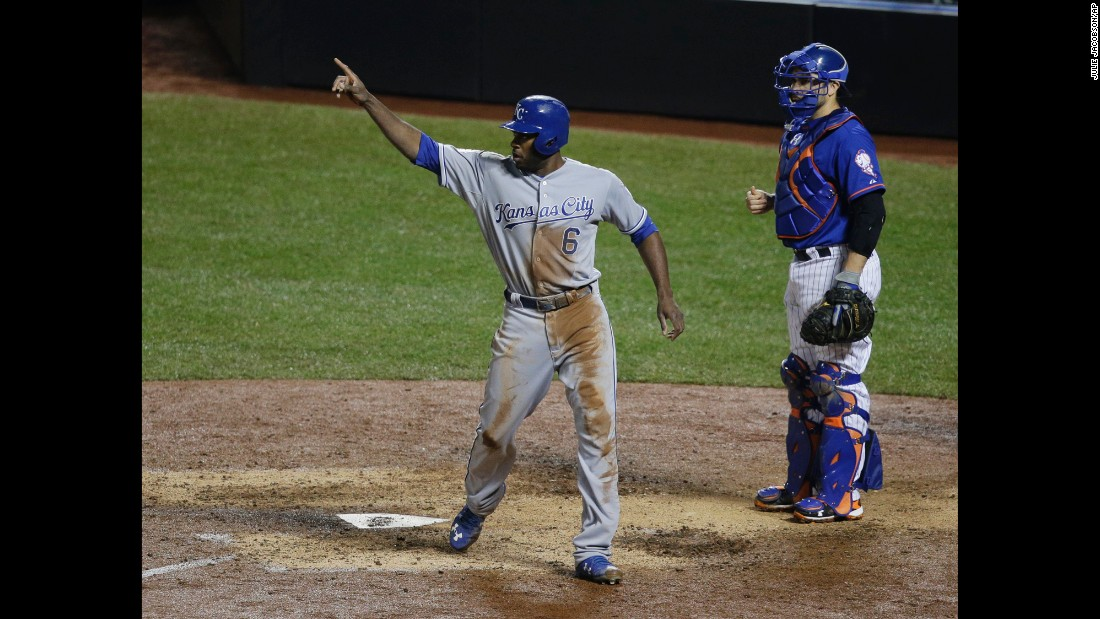 New York Mets catcher Travis d'Arnaud watches as Kansas City Royals' Lorenzo Cain signals to Eric Hosmer after Hosmer's RBI double during the ninth inning.