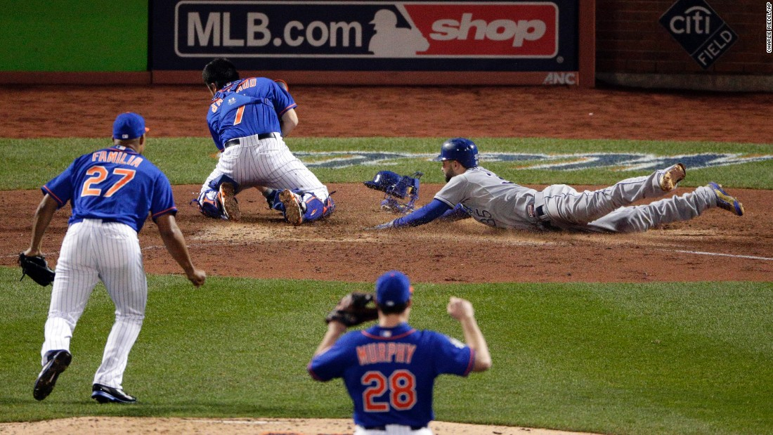 Kansas City Royals' Eric Hosmer right, scores past New York Mets catcher Travis d'Arnaud during the ninth inning.