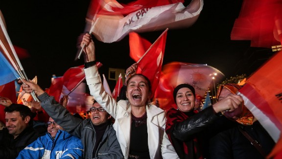 ANKARA, TURKEY - NOVEMBER 01: People wave flags outside the ruling AK Party headquarters after the party won a critical election after loosing a majority back in June on November 1, 2015, in Ankara, Turkey. Polls have opened in Turkey's second general election this year, with the ruling Justice and Development Party (AKP) hoping to win a majority, as the country searches for stability amongst serious security concerns. (Photo by Burak Kara/Getty Images)