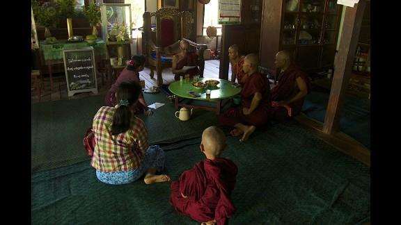 People sit at the Buddhist monastery Meiktila Burma, where U Wie Douktah gave shelter to Muslims in 2013.