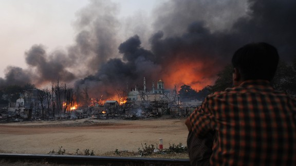 A resident watches as black smoke rises from burning houses  in riot-hit Meiktila, central Myanmar on March 21, 2013.  At least 10 people were killed in riots in central Myanmar.