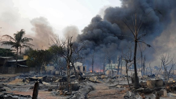 Black smoke rises from burning houses around a mosque in riot-hit Meiktila, central Myanmar on March 21, 2013.