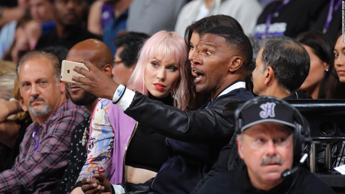 Actor Jamie Foxx snaps a picture of himself during an NBA basketball game in Sacramento, California, on Wednesday, October 28. Singer Natasha Bedingfield, in the pink hair, joined Foxx for the front-row selfie.