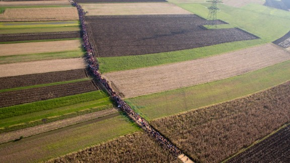 A column of migrants moves along a path between farm fields in Rigonce, Slovenia, in October 2015.