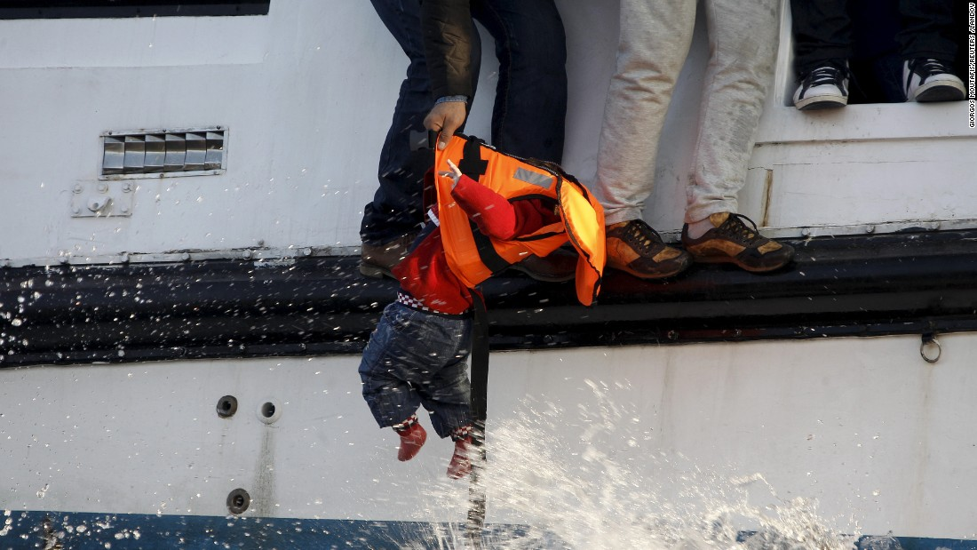 "A refugee prepares to hand a toddler to a volunteer lifeguard as a half-sunken catamaran arrives at the Greek island of Lesbos on Friday, October 30. There were about 150 refugees on the boat, mostly Syrians. According to the U.N. refugee agency, more than 744,000 refugees and migrants <a href=""http://www.cnn.com/2015/09/03/world/gallery/europes-refugee-crisis/index.html"" target=""_blank"">have escaped to Europe</a> this year."