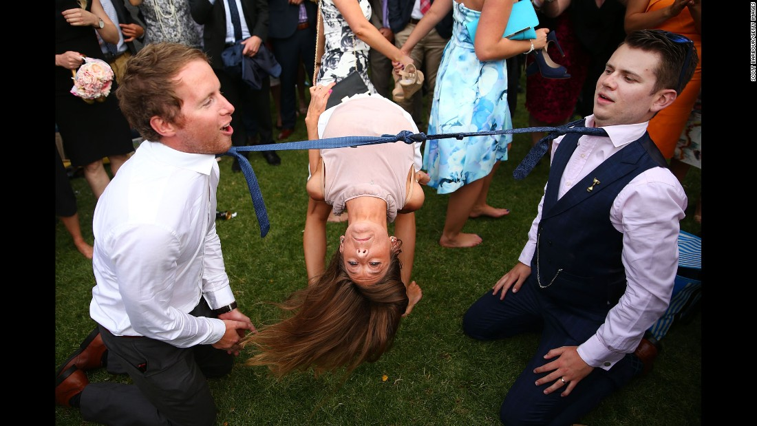 A woman takes part in a game of limbo while attending the Melbourne Cup horse races in Australia on Tuesday, November 3.
