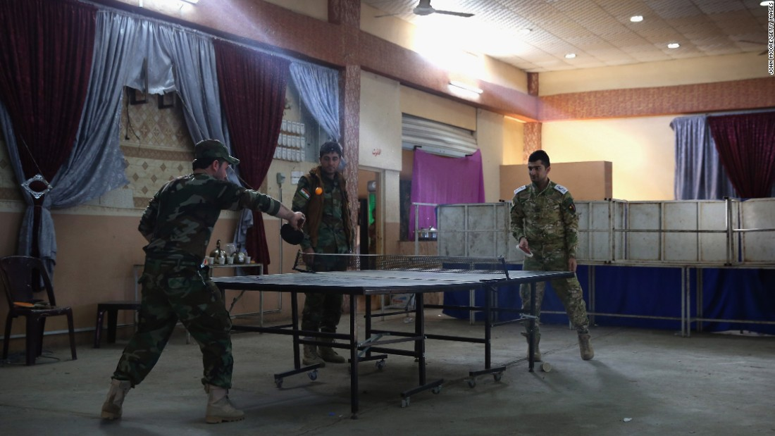 Peshmerga fighters play table tennis Wednesday, November 4, in a wedding hall that now serves as a military hospital in Telskuf, Iraq. The Peshmerga frequently come across mortar fire from ISIS militants just 2 miles away.