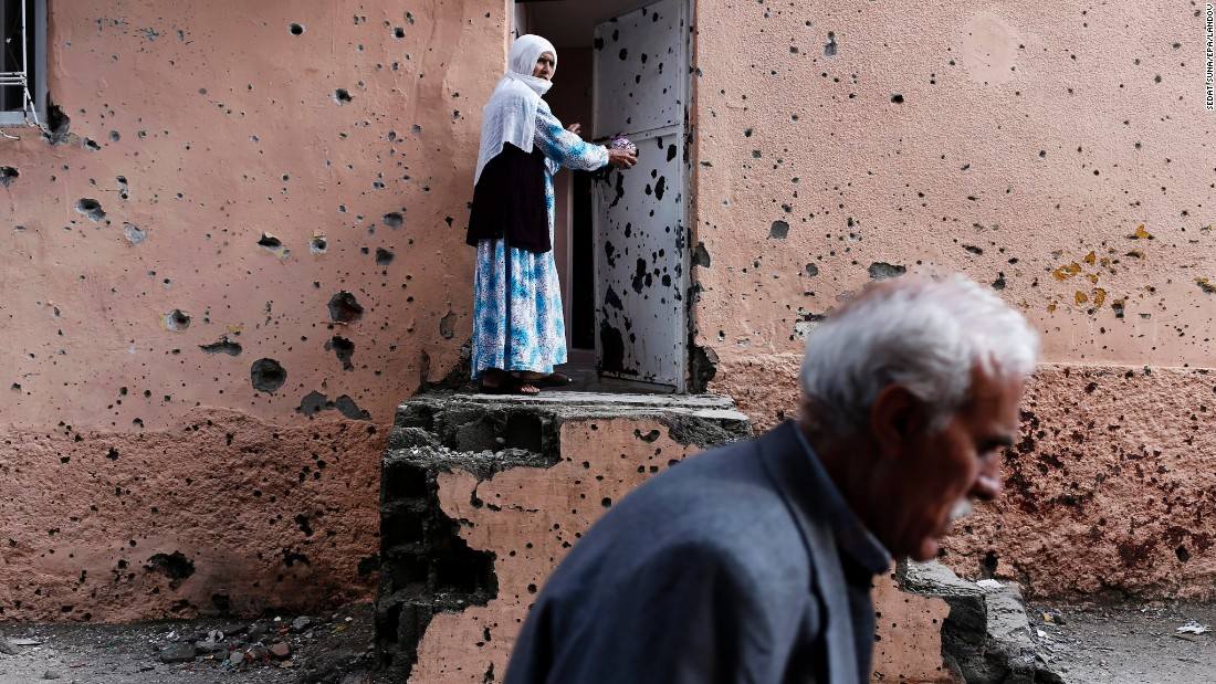 A Kurdish woman waits outside her house in Diyarbakir, Turkey, on Friday, October 30. The house's wall is riddled with bullet holes after clashes between Turkish armed forces and the Kurdistan Workers' Party.
