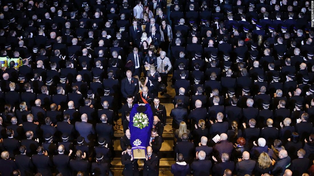 The coffin of police officer Dave Phillips is carried out of a church following a funeral service in Liverpool, England, on Monday, November 2. Phillips, 34, was killed in a hit-and-run last month.