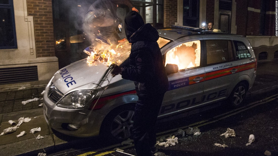 A police car is burned during the anti-capitalist Million Mask March near the British Houses of Parliament in London on Thursday November 5. The hacker group Anonymous organized the protest.