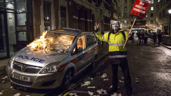 An unattended police car is set on fire in Queen Anne's Gate in central London during the protest on Guy Fawkes Night, an annual commemoration in the UK of a failed plot to kill King James I in 1605.