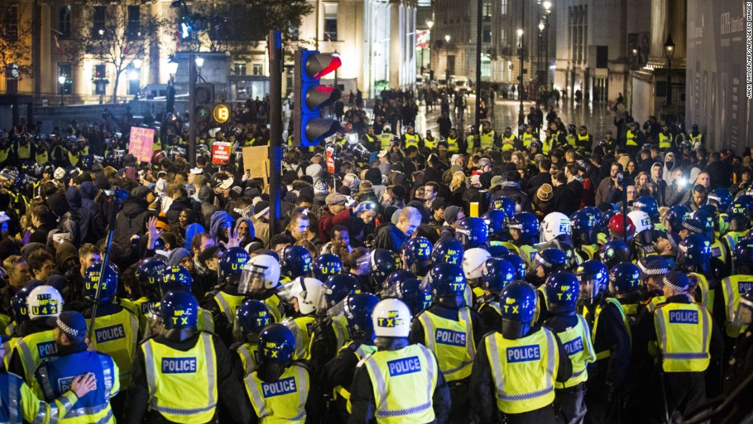 British police officers form a blockade around protesters during the Million Mask March.