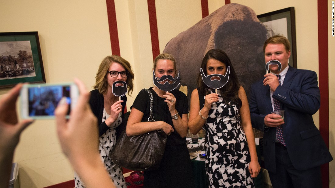 "Staffers on Capitol Hill pose with masks at the National Bison Day Reception on Wednesday, November 4. The ""Beards for Bison"" campaign encourages people to wear their ""fur"" to show support for the species."