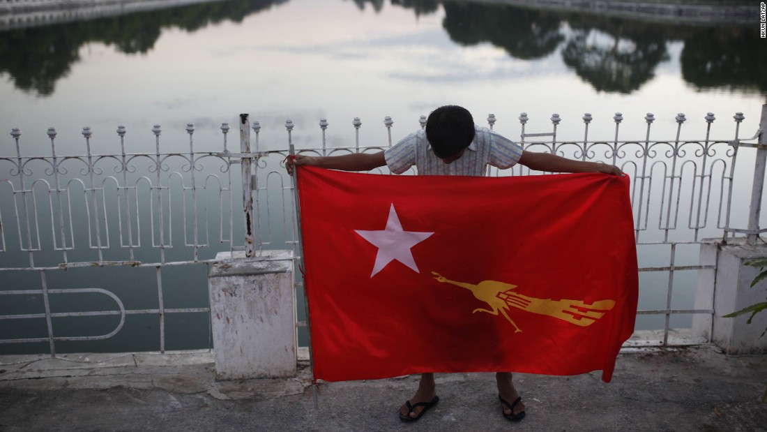 A supporter of Aung San Suu Kyi's National League for Democracy party holds a party flag in Mandalay on November 5.
