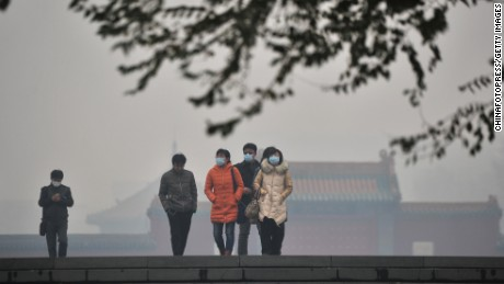 Citizens wearing masks walk in the smog at the Mukden Palace on November 8, 2015 in Shenyang, Liaoning Province of China.
