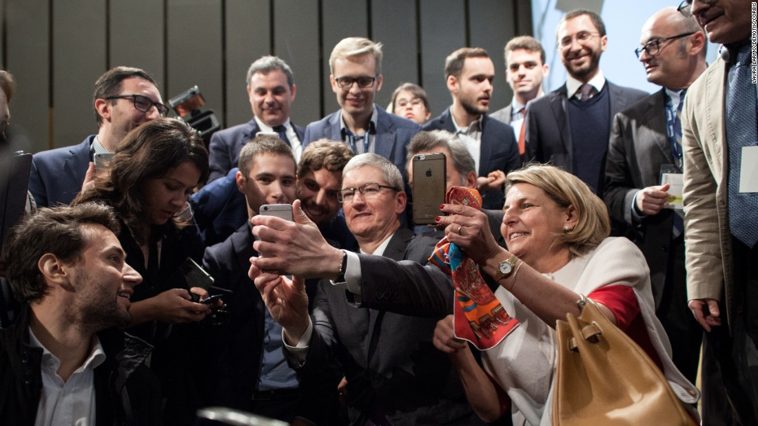 Apple CEO Tim Cook holds his phone as he takes a selfie Tuesday, November 10, at Bocconi University in Milan, Italy. Cook was a guest speaker at the school.