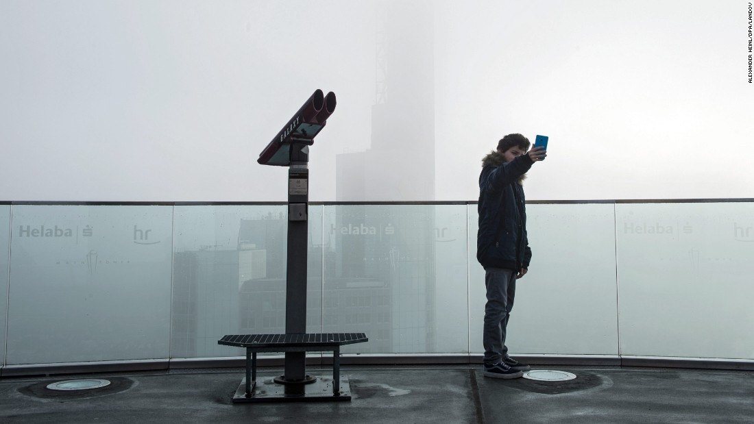 A visitor at the Main Tower skyscraper takes a selfie of the fog-covered skyline in Frankfurt am Main, Germany, on Wednesday, November 4.