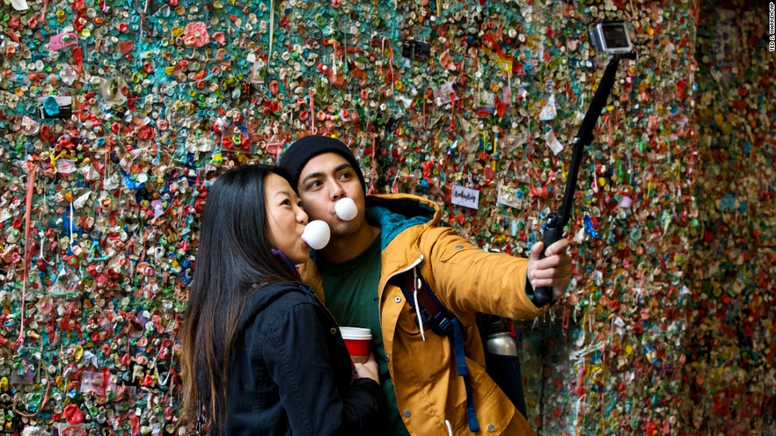 "Two visitors take a selfie at the famous ""gum wall"" in Seattle on Monday, November 9. The wall, which had accumulated people's gum over 20 years, <a href=""http://www.cnn.com/2015/11/04/travel/seattle-pike-place-gum-wall-cleaning-feat/"" target=""_blank"">was scheduled for a deep cleaning.</a>"