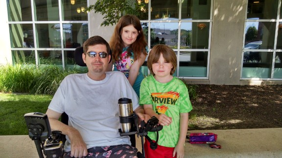 """Masters sits with Sabrina and Radley in June 2015.  """"The ALS Association told us you have to stay in front of this disease. Don't wait until it's an emergency,"""" he says. """"We've done some voice banking.  I'm using feet on my laptop and when they quit working I'll need the eye gaze machine or NeuroSwitch. Denial is going to get you in trouble. You have to be proactive and have the next stage of tools ready when you need them."""""""