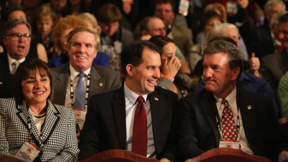 Wisconsin Gov. Scott Walker, center, sits in the audience. He dropped out of the presidential race in September.