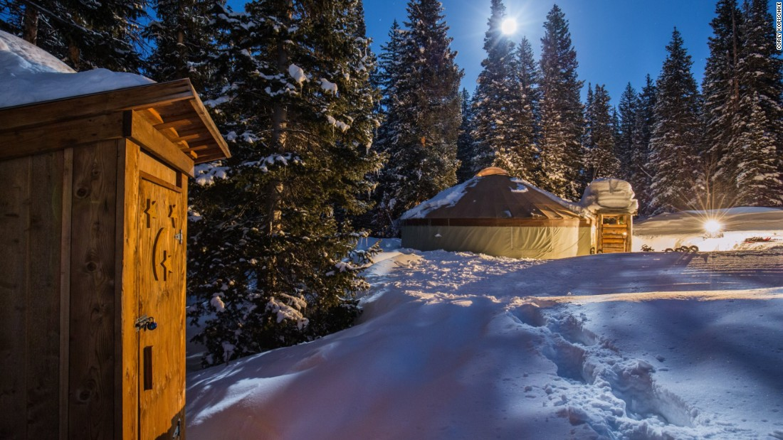 Illuminated by lanterns and moonlight, the yurt is set in a forest clearing, surrounded by tall pine trees.