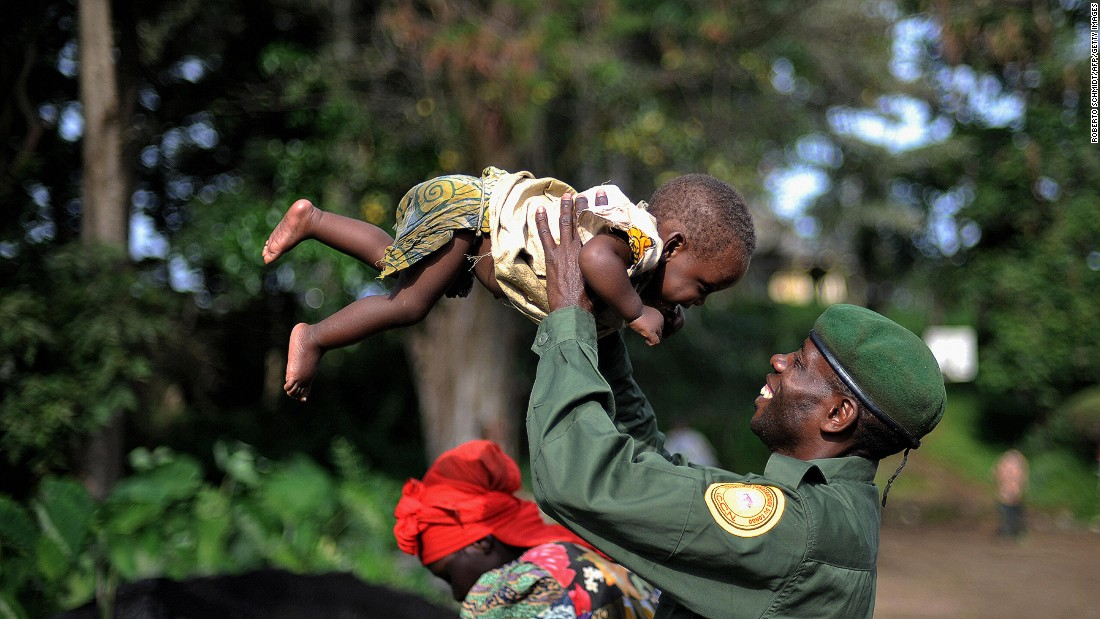 A park ranger, working in the Virunga National Park, smiles at his 9-month-old daughter after he, and other park ranger families, came back to their homes in Rumangabo in 2008. The rangers and their families had to flee their homes after heavy clashes between armed groups broke out in and around the park.