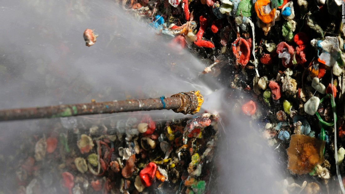 A worker uses a high-temperature pressure washer to clean layers of gum from Seattle's famous gum wall at Pike Place Market on Tuesday, November 10. Tourists and locals have been sticking their used chewing gum on the walls of a section of Post Alley for the past 20 years.