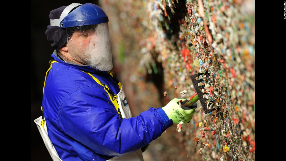 Fernando Soberania uses a tool to scrape layers of gum from the wall.