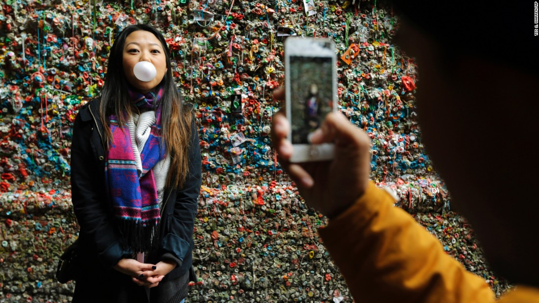 A tourist has her photo taken in front of the gum wall before the deep clean.