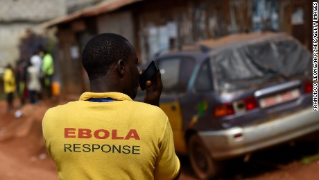 "An UN World Food Program's staff wearing a t-shirt reading ""Ebola response"" uses a cellphone during a supplies' delivery operation  in Lester Road in Freetown, on November 7, 2014. on November 7, 2014. West Africa's regional bloc on November 7 called for international help to go beyond immediate medical care for Ebola-hit nations, warning that lives had been blighted by the epidemic. The raging Ebola outbreak has likely killed far more people than the 4,818 deaths reported by the World Health Organization, an expert at the UN health agency said on November 6, warning that thousands of fatalities were likely not accounted for. AFP PHOTO/ FRANCISCO LEONG        (Photo credit should read FRANCISCO LEONG/AFP/Getty Images)"