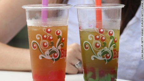 A young woman and a friend enjoy bubble tea outside a cafe. Bubble tea, which fuses Asian tea with milk or fruit syrups and sometimes contains balls of tapioca, originated in Taiwan and has most recently spread in popularity to North America and Europe, in addition to Malaysia.