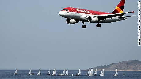 In the forefround  an Avianca airliner lands in the Santos Dumont airport (not framed) as sailing boats compete in the International Sailing Regatta held in the Guanabara Bay in Rio de Janeiro, Brazil on August 19, 2015, an event that serves as a test for the Rio 2016 Olympic Games.    AFP PHOTO/VANDERLEI ALMEIDA        (Photo credit should read VANDERLEI ALMEIDA/AFP/Getty Images)