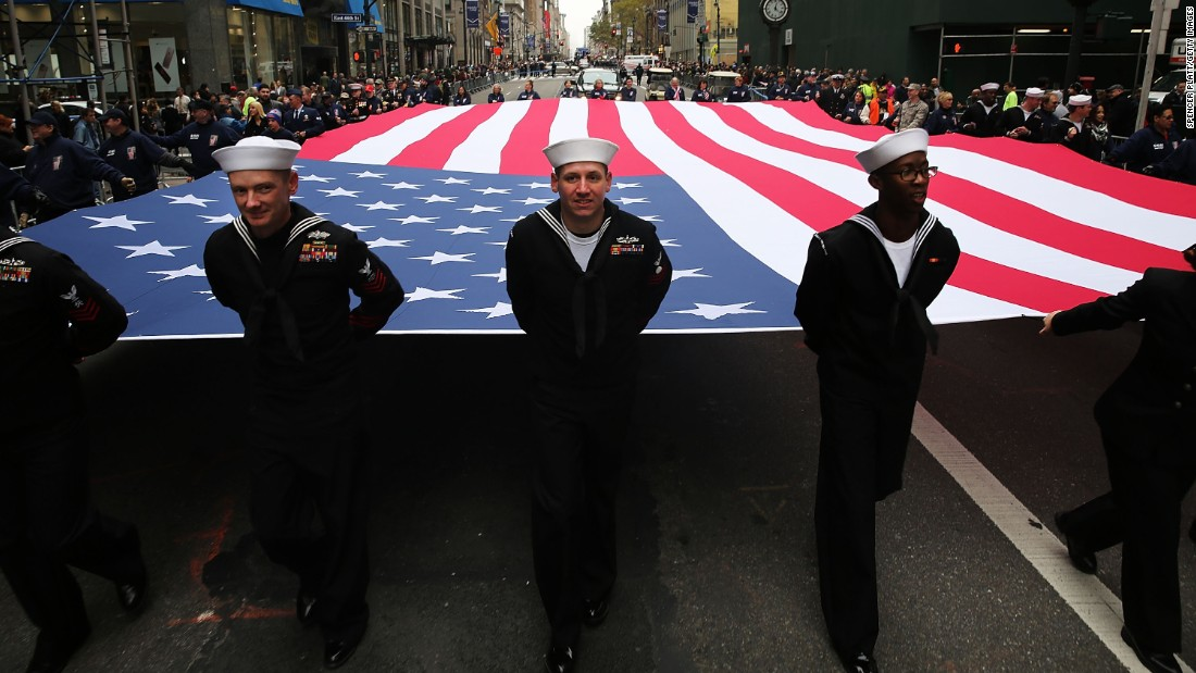 Members of the U.S. Navy march with the American flag during a Veterans Day parade in New York City on Wednesday, November 11.
