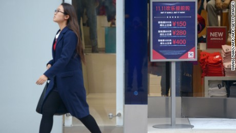 "A woman walks past a ""Singles Day"" sale promotional board at the entrance of a shop in Beijing on November 11, 2015.  Shoppers spent around 9 billion USD in the first 12 hours of China's ""Singles Day"" sale on November 11, e-commerce giant Alibaba said, in the world's biggest online shopping day.         AFP PHOTO / WANG ZHAOWANG ZHAO/AFP/Getty Images"