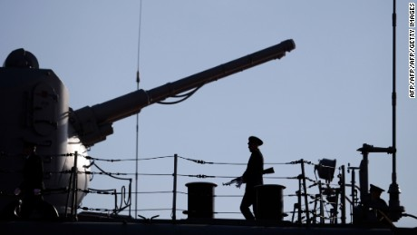 A Russian Navy member stands guard on the deck of the Pyotr Velikiy (Peter the Great) Russian nuclear-powered missile cruiser docked in the Cypriot port of Limassol, on February 12, 2014. The Russian ship is part of the team involved in escorting shipments of Syria's chemical weapons material for destruction. AFP PHOTO / YIANNIS KOURTOGLOU        (Photo credit should read Yiannis Kourtoglou/AFP/Getty Images)