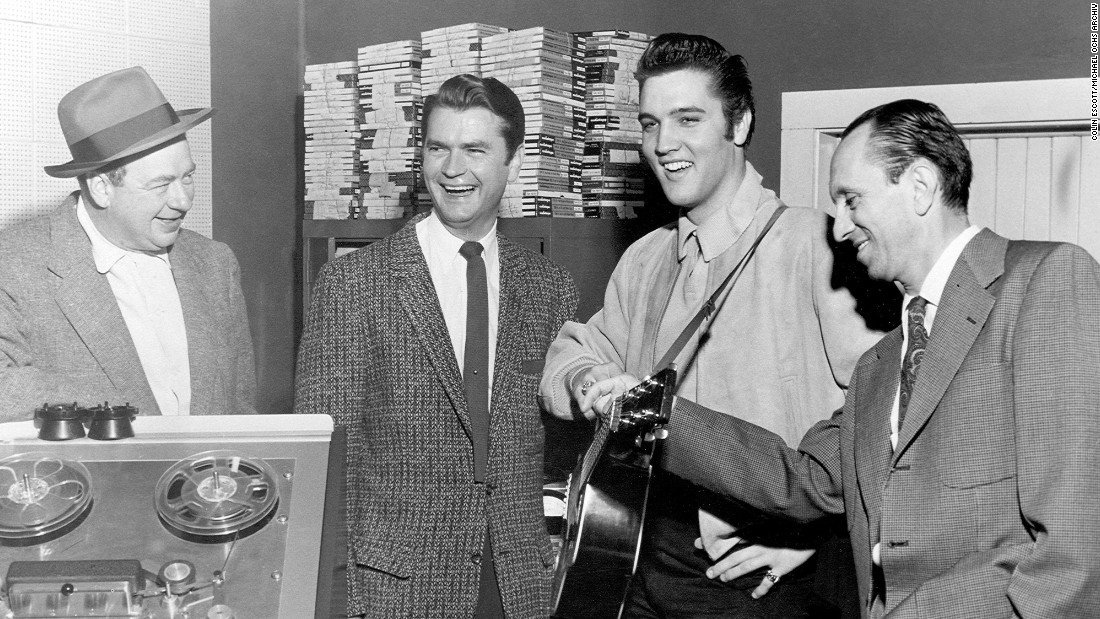 "Phillips' most important find was Elvis Presley, who first wandered into the studio in 1953. The next year, Phillips started producing his sides, and such songs as ""That's All Right,"" ""Baby Let's Play House"" and ""Trying to Get to You"" made him a star. Phillips sold Presley's contract to RCA in late 1955 for $35,000 -- considered an outrageous sum. The rest, however, is history. He poses here with reporter Leo Soroka, Phillips and reporter Robert Johnson in 1956."
