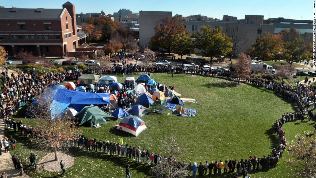 "University of Missouri students circle tents on the Carnahan Quad, locking arms to prevent media from entering the space, following <a href=""http://www.cnn.com/2015/11/09/us/missouri-football-players-protest-president-resigns/"" target=""_blank"">the resignation</a> of President Timothy W. Wolfe on Monday, November 9."