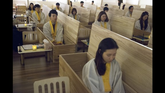People sit in wooden coffins at the Hyowon Healing Center in Seoul, South Korea. It's where groups of people who might be struggling with depression, stress or suicidal thoughts go to act out their own funerals. After the emotional, personal experience, some seemed to leave feeling happier, photographer Françoise Huguier said.
