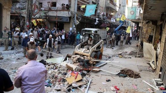 Lebanese municipality workers clear debris from the site of a twin bombing attack in the area of Burj al-Barajneh in Beirut