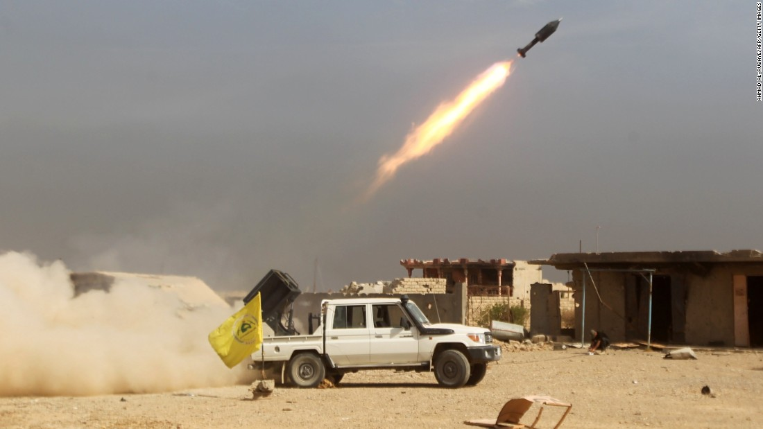 Shiite fighters, fighting alongside Iraqi government forces, fire a rocket at ISIS militants as they advance toward the center of Baiji, Iraq, on Monday, October 19.