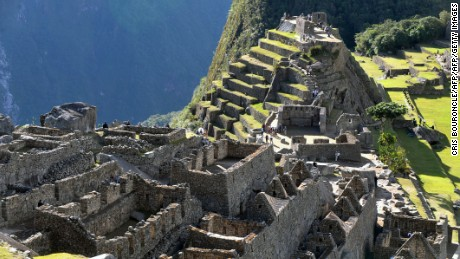 Tourists walk among the ruins of the Machu Picchu citadel, 130 km northwest of Cusco, Peru on July 6, 2011. The Inca compound is being prepared for the centennial commemoration of its discovery by American adventurer and archaeologist Hiram Bingham in 1911. Machu Picchu recognized as a World Wonder in 2007 sits at 2,350 meters above sea level in the heart of the Urubamba valley in southern Peru, 510 kilometers south of Lima. The complex which remained unknown to Spanish conquerors is now visited by up to 250,000 a year. AFP PHOTO/Cris BOURONCLE (Photo credit should read CRIS BOURONCLE/AFP/Getty Images)