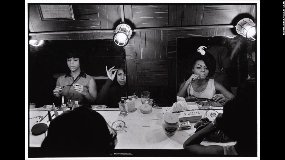 "The Supremes prepare for a show at New York's Apollo Theater in 1965. The singing group had several hit songs that year, including ""Stop! In the Name of Love,"" ""Back in My Arms Again"" and ""I Hear a Symphony."" Bruce Davidson photographed the Supremes in New York and Detroit. ""I was able to come close and personal because somehow they trusted my eye,"" he said 50 years later. ""They allowed me, with my little Leica camera, to photograph. ... Whether it was performing, whether it was looking at themselves in the backstage mirror or whether it was resting between performances, sitting on a bed, I was allowed and no one closed any doors."""