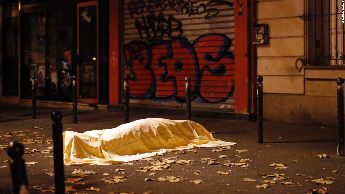 A body, covered by a sheet, is seen on the sidewalk outside the Bataclan theater.