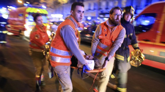 A woman is being evacuated from the Bataclan theater after a shooting in Paris, Friday Nov. 13, 2015.  French President Francois Hollande declared a state of emergency and announced that he was closing the country's borders. (AP Photo/Thibault Camus)