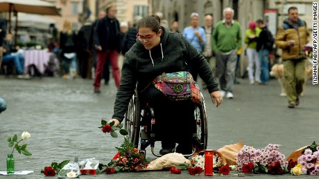 A woman brings flowers outside the French Embassy in Rome on November 14, a day after deadly attacks in Paris.