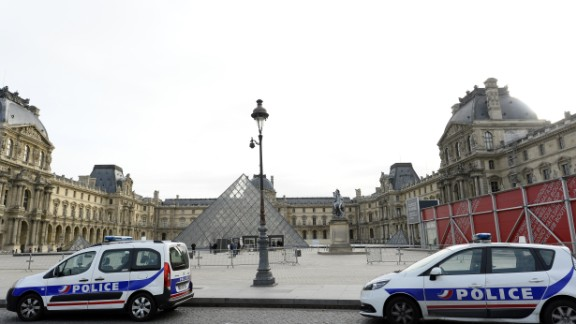 Police vehicles are parked near the entrance to the Louvre in Paris on November 14. Interior Minister Bernard Cazeneuve said the state of emergency in France could mean restrictions on people's movements. Airports in France remained open, and airlines were still flying there, though some airlines reported canceled flights.