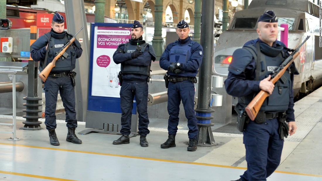 Police stand guard at a train station in Paris on November 14.