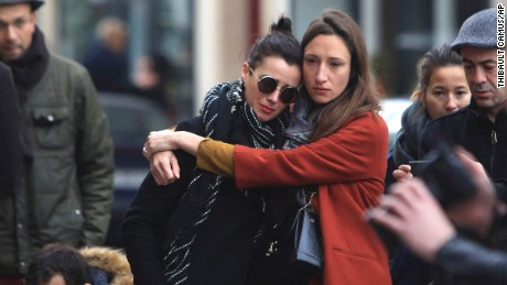 Women comfort each other as they stand in front of the Carillon cafe, in Paris, Saturday, November 14 following Friday's terror attacks.