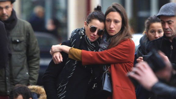 Women comfort each other as they stand in front of the Carillon cafe, in Paris, Saturday, November 14 following Friday
